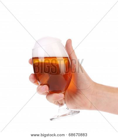 Hand holds glass of beer.