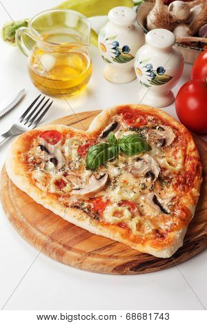 Heart shaped funghi pizza with hot peppers, classic italian recipe