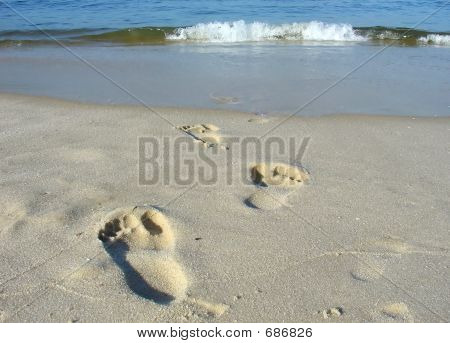 Footprints On The Beach Sand