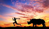 Man running away from rhino at sunset in savanna poster