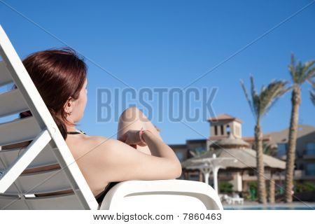 Woman Relaxing In Deck Chair At Resort