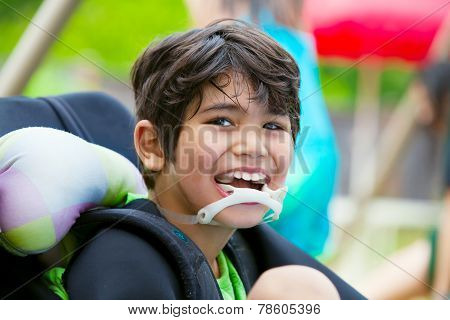 Disabled Eight Year Old Boy In Wheelchair Smiling