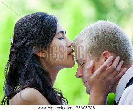 Biracial bride kissing Caucasian groom on forehead