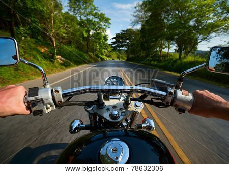 Driver riding motorcycle on an asphalt road through forest poster