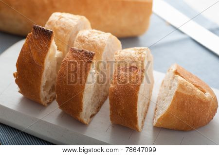 Close up of sliced Turkish Bread on white wooden cutting board poster