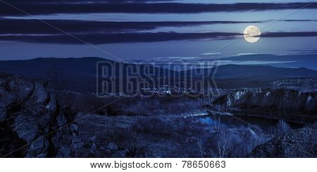 Lake In Mountains Quarry Near City At Night