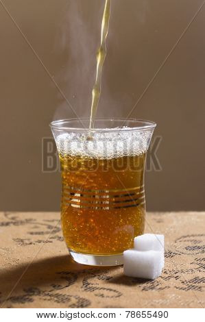 Pouring of tuareg the moroccan mint tea into a glass and two sugar cubes prepared for sweetening the tea. poster