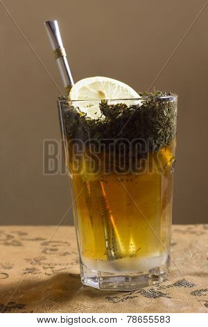 Close-up Of Glass Of Tea With Slice Of Lemon And Bombilla