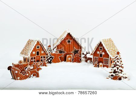 The family near hand-made eatable gingerbread house and New Year Trees with snow decoration poster