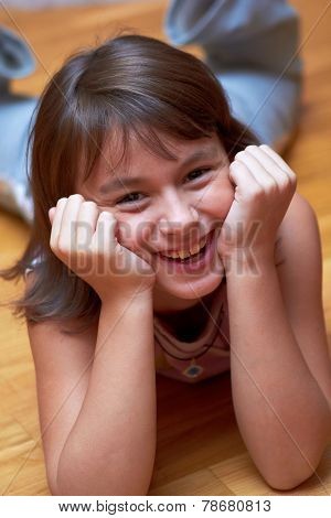 smiling girl lying on the floor resting his head in hands