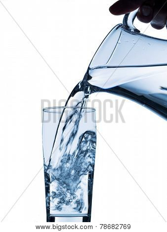 pure water is emptied into a glass of water from a jug. fresh drinking water poster
