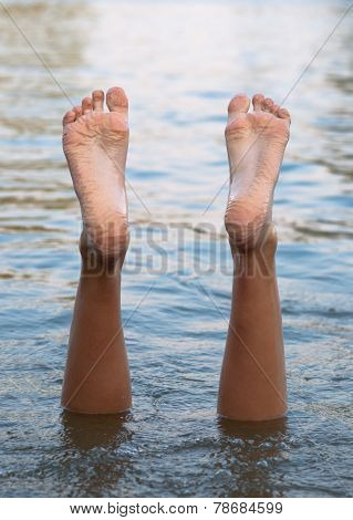 Female legs and feet upside down in the water