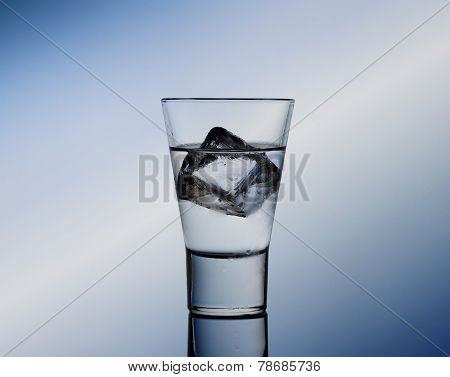 Short Drink Glass With Clear Liquid And Ice Cubes