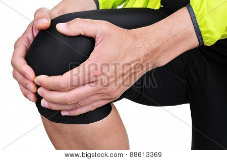 closeup of a young caucasian sportsman wearing sport clothes with his hands in his knee because of his knee pain