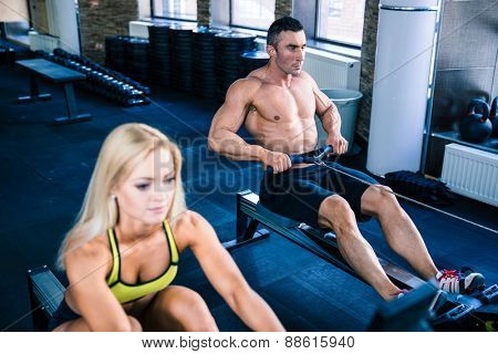 Muscular man and sporty woman doing exercises on training simulator in crossfit gym. Focus on man