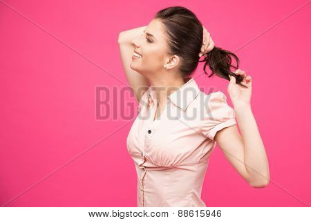 Side view portrait of a smiling woman holding her hair over pink background