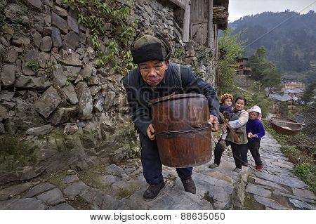 Chinese Older Man Climbs Stone Mountain Road With Wooden Barrel
