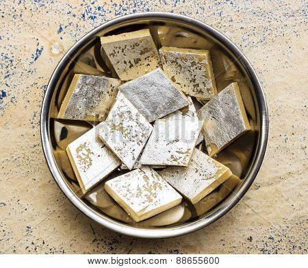 Kaju katli ~ Indian sweets made from cashew nut paste kept in a vessel on a abstract background