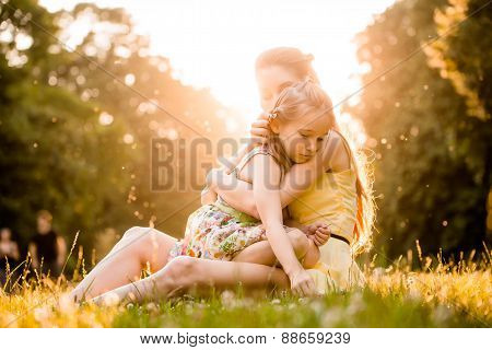 Mother is cuddling her worried child outdoor in nature poster