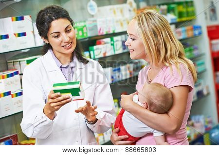 pharmacist chemist woman giving vitamins to mother with child in pharmacy drugstore poster