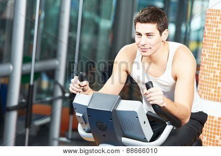 young man at cardio training on bicycle machine station in fitness gym