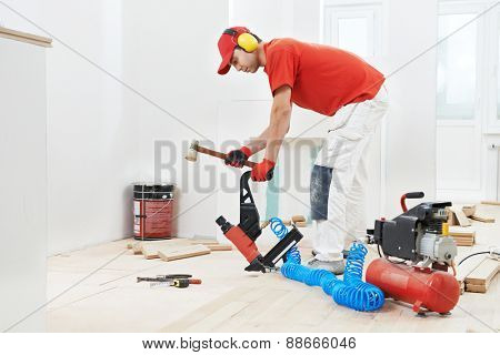 carpenter worker installing wood floor parquet board during flooring work with hammer poster