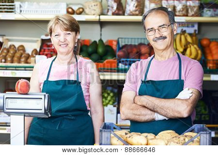 adult senior sale man with female assistant in fruit vegetable market shopping store