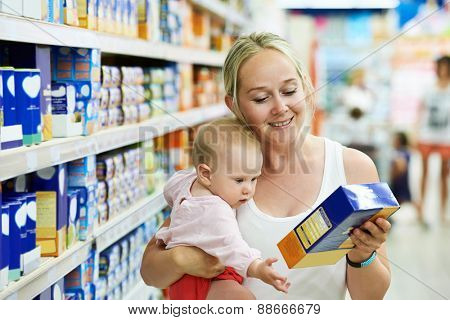 woman choosing children food with little baby child girl on hands during supermarket shopping