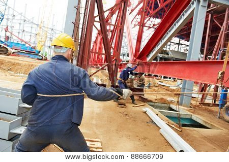 builder worker at construction site installing metal construction frames