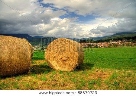 hay bales on green grass under a cloudy blue sky