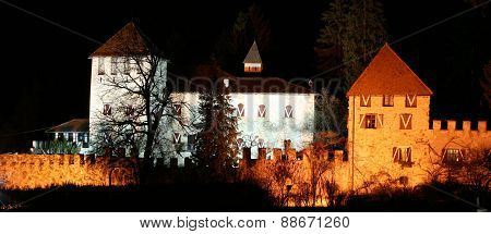 Castle by night illuminated with white and orange  light.