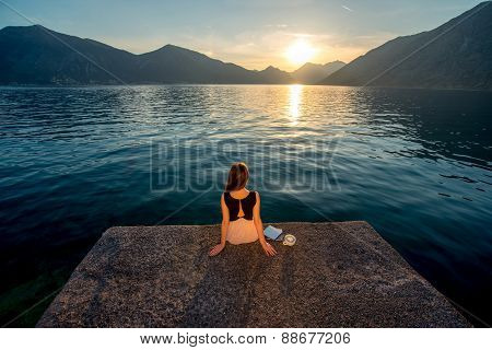 Woman sitting on the pier at sunrise