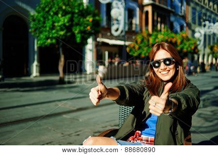 Beautiful Young Asian Multiracial Causal woman In Sunglasses At Cafe In City Giving You Two Thumb Up