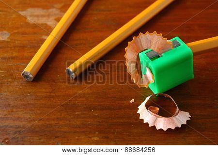 Pencil in a sharpener and two unsharpened pencils