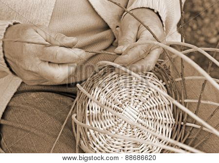 Expert Hands Of The Elderly Craftsman Creates A Woven Wicker Basket