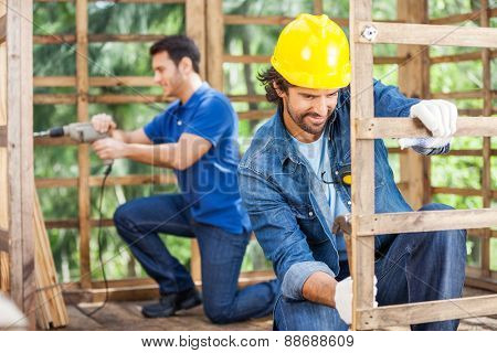 Male worker hammering while colleague drilling wooden cabin at construction site
