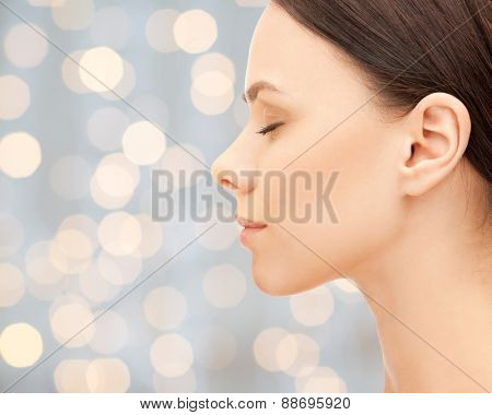 health, people and beauty concept - beautiful young woman face over holidays lights background