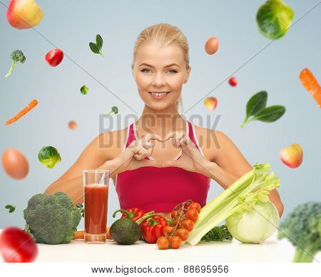 people, healthy eating, vegetarian and health care concept - happy woman with organic food and falling vegetables showing heart shape symbol over gray background