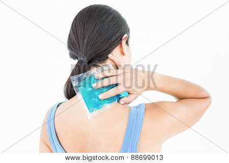 Beautiful brunette putting gel pack on neck on white background poster