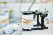 prosthetic dentistry concept. Articulator with dental prosthesis model in laboratory poster