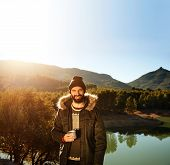 Strong hiker standing on the mountain near lake in background and resting with hot coffee. Happy multiracial smiling man outdoors. Lifestyle photo of Caucasian breaded man. poster