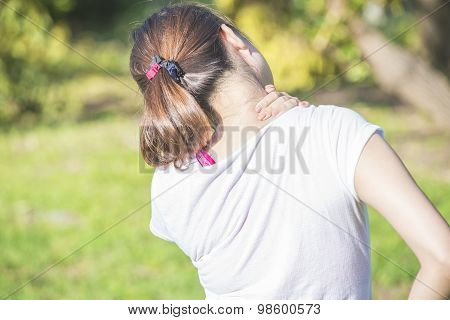 young woman in sportswear touching her neck and lower back muscles by painful injury