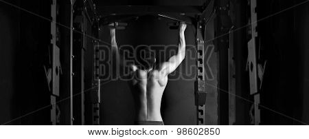 Muscle athlete man in gym making elevations