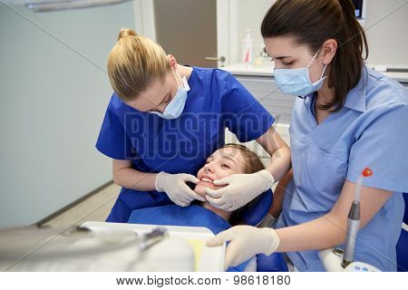 people, medicine, stomatology and teeth care concept - happy female dentist with assistant checking patient girl dental occlusion teeth at dental clinic office