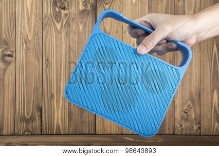 Man's Hand Carrying Blue Handy Speaker On Wooden Background