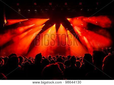 silhouettes of concert crowd in front of bright stage lights - a small depth of field signifies that the focused area is narrow