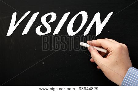 Male hand wearing a business shirt writing the word Vision in white text on a blackboard poster