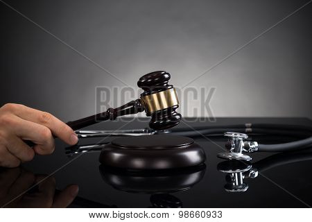 Close-up Of Hands With Gavel And Stethoscope