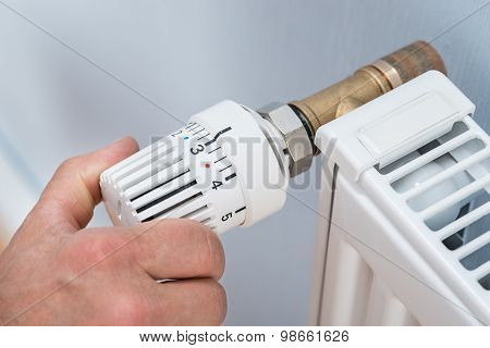 Person Adjusting Temperature Of Radiator Thermostat