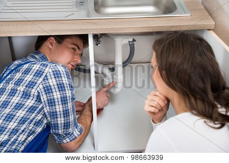 Plumber Showing Damage In Sink Pipe To Woman Plumber At Home poster
